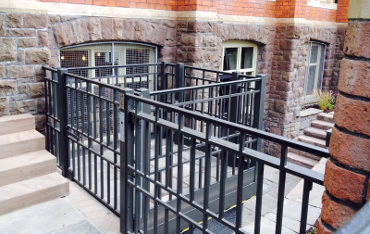 External access platform with inset stone pavers including architectural handrails and gates