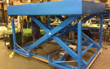 Hydraulically operated adjustable rising support legs for scissor lift table