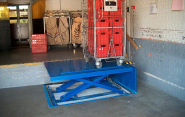 Low closed lift in loading bay for handling roll cages of mail